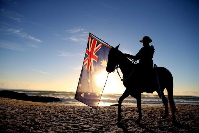 Man on horse holding an Australian flag on the beach.