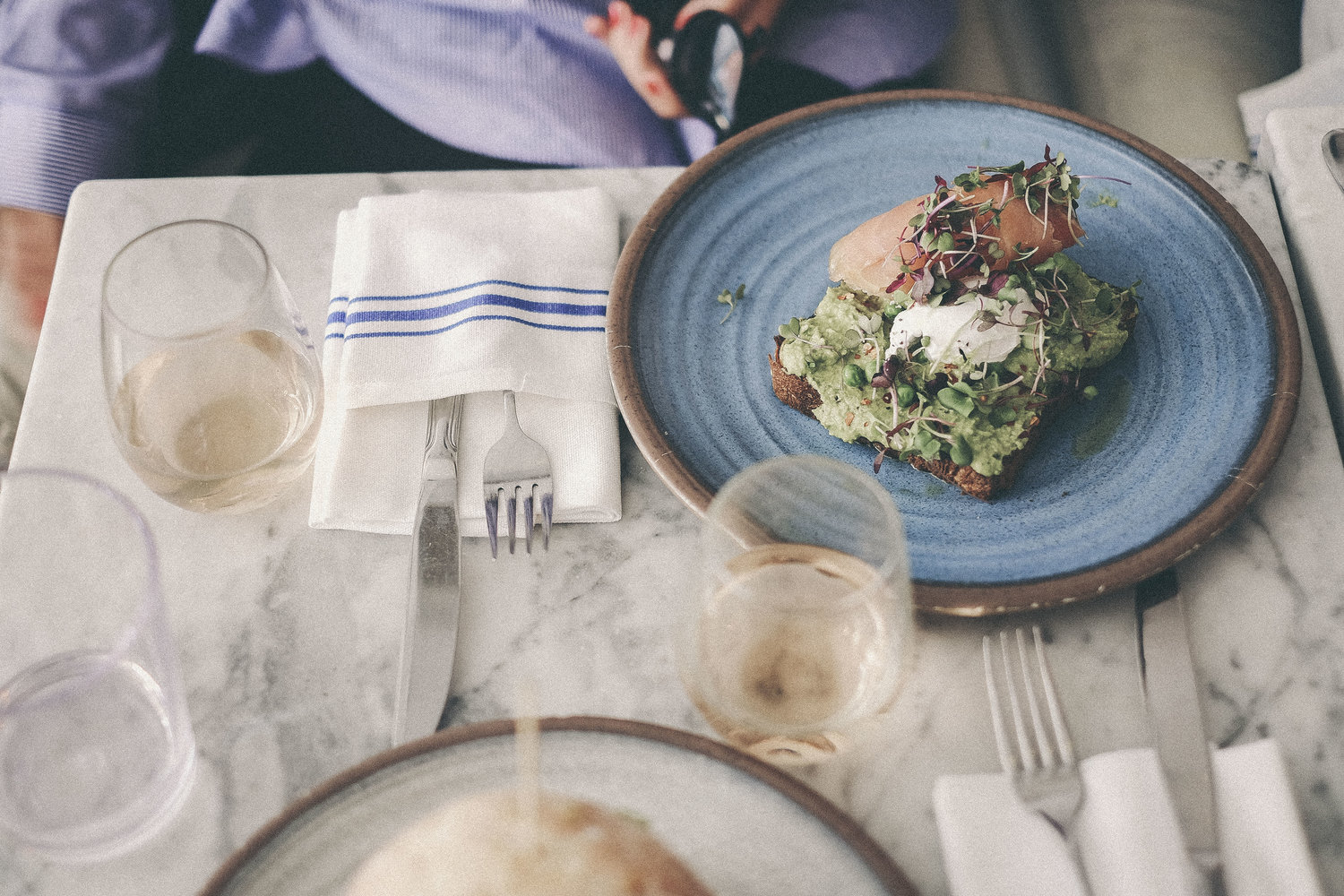 Table top at Bluestone Lane with white wine and an Avo Smash with an egg and smoked salmon.