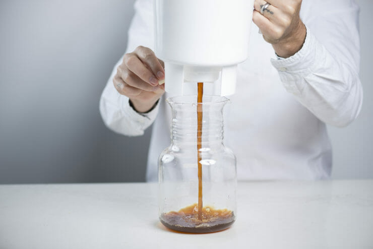 someone pouring cold brew into a clear jar.