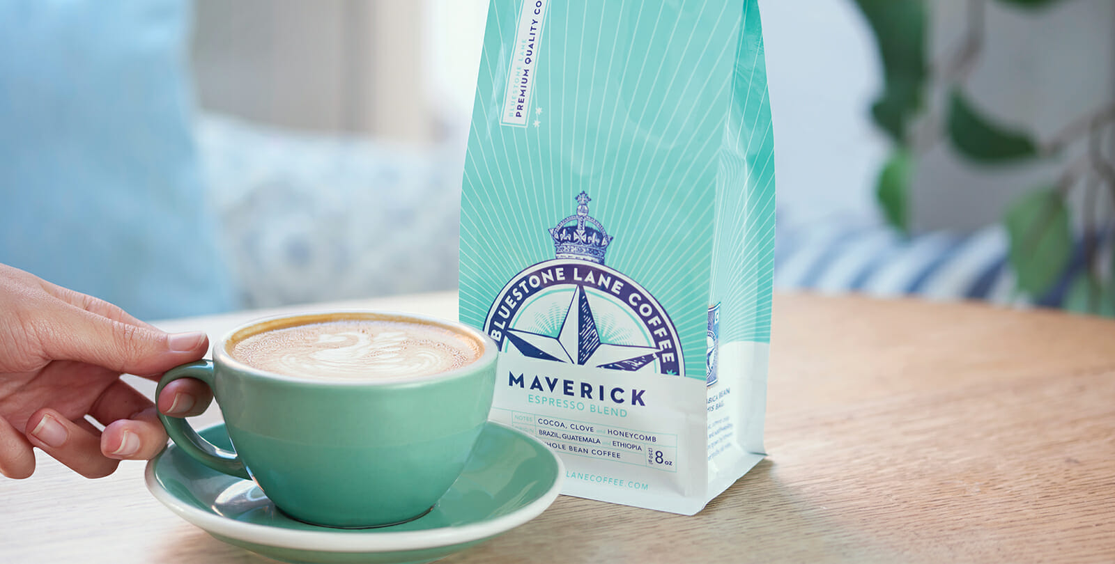bag of Maverick coffee on table next to cup of flat white, hand reaching for cup